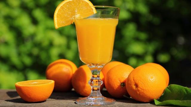 Orangen liegen auf einem Holztisch, davor steht ein Glas Orangensaft