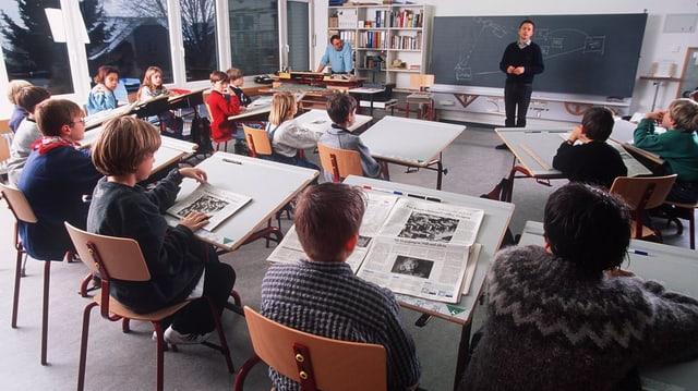 In einer Schulklasse sitzen die Schüler und Schülerinnen an ihren Pulten undarbeiten. Im Hintergrund steht der Lehrer vor der Wandtafel.