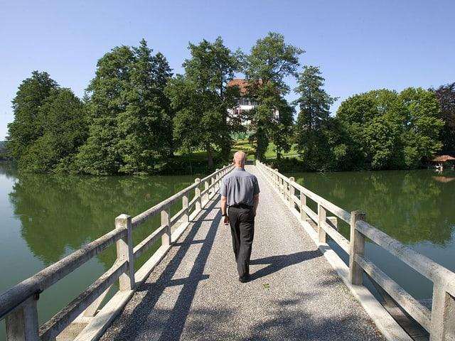 Uli Sigg läuft über eine Brücke auf die Insel.