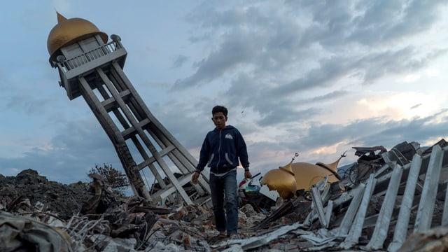 Junger Mann inmitten von Trümmern.