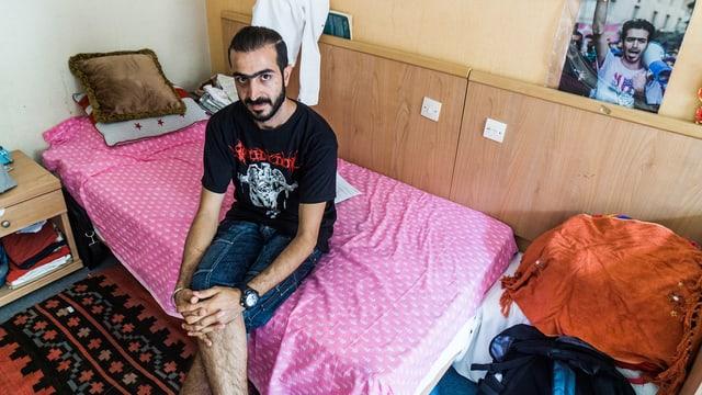 Ein Mann sitzt mit übereinandergeschlagenen Beinen auf dem Bett eines Hotelzimmers.