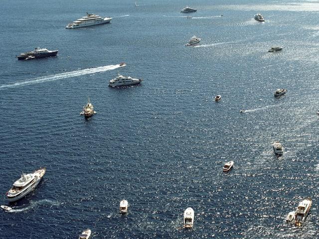 Ein Dutzend Schiffe und Jachten schwimmen aus Vogelperspektive auf dem Meer.