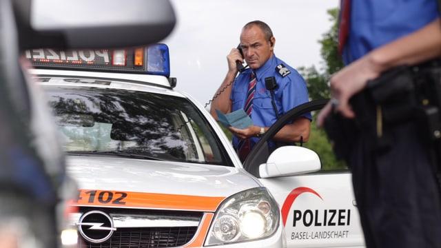 Ein Polizist steht beim Polizeiauto und hält einen Hörer in der Hand. Im Vordergrund sieht man einen zweiten Polizisten, unscharf.