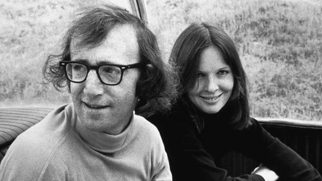 Foto schwarzweiss: rechts eine Fraue mit langen Haaren und verschränkten Armen, lächelt in die Kamera. Links ein Mann mit Hornbrille und mittellangem Haar schaut aus dem Bild und lächelt leicht.