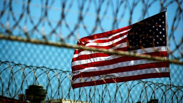 Hinter einem Zaun aus Maschendraht weht die amerikanische Flagge.