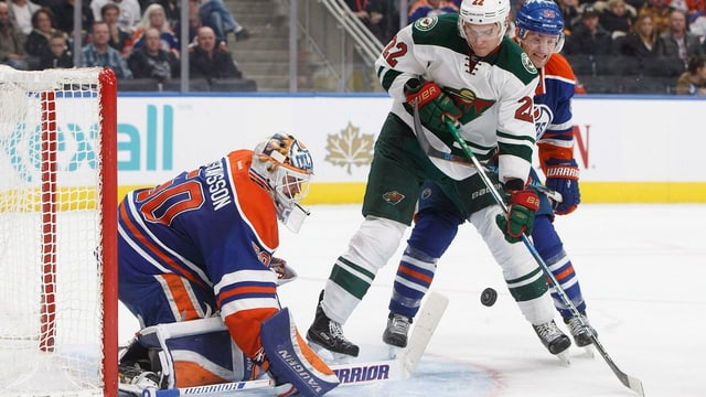 Nino Niederreiter e Edmonton Oilers' Mark Letestu en cumbat avant il goalie Jonas Gustavsson.