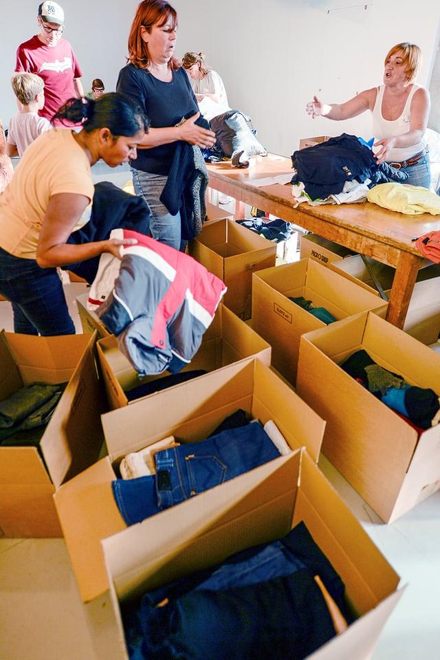 Freiwillige der privaten Hilfsaktion «Tsueri hilft» beim Aussortieren von Kleidern.