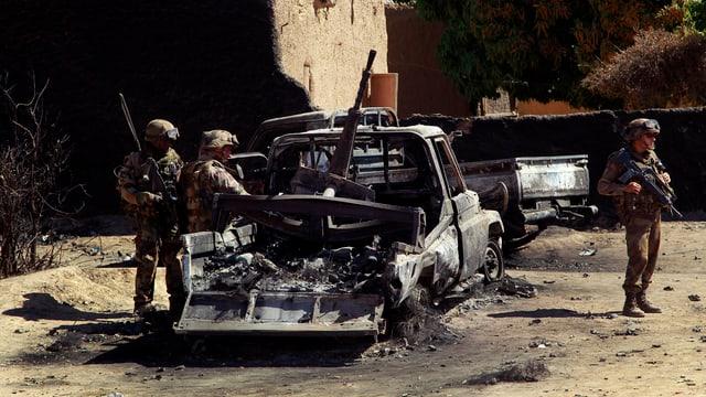 Soldaten vor einem ausgebrannten Pick-Up.
