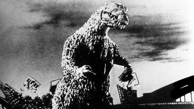 Ein Still aus dem Godzilla-Film: Godzilla zerstört eine Brücke.