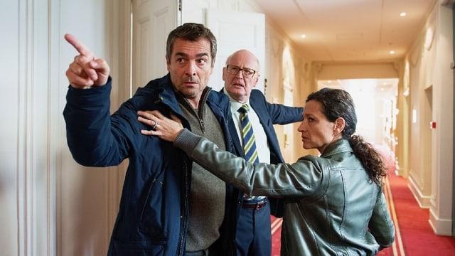Ein Mann mit wütendem Blick und erhobenem Zeigefinger wird von einer Frau zurückgehalten. Dahinter steht ein weiterer Mann, der aufgebracht aussieht.