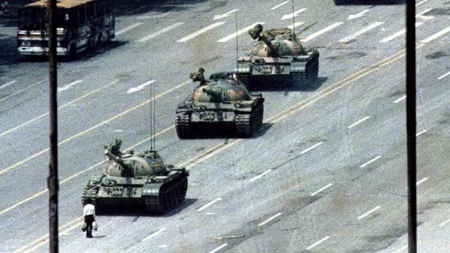 Panzer. Davor steht ein Mensch. Es ist ein historisches Bild von 1989.