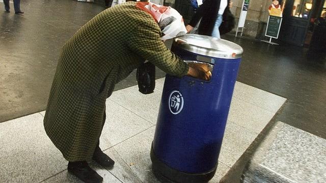 Eine alte Frau durchsucht einen Abfalleimer.