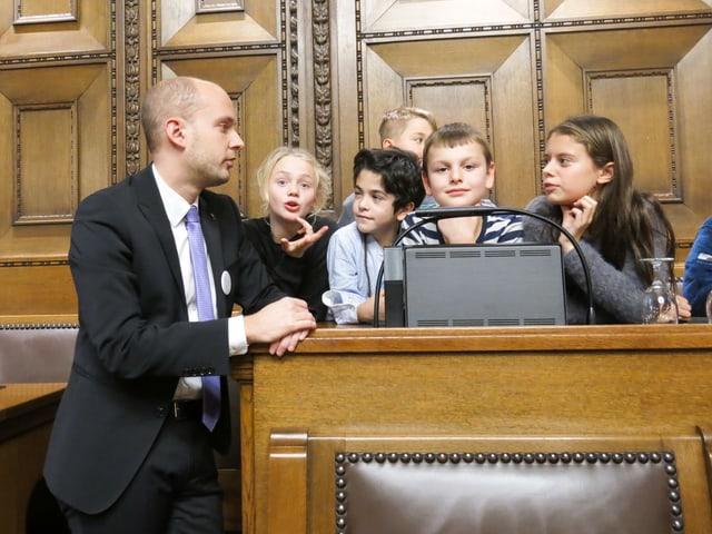 Joël Thüring steht neben den kindern, die an seinem Platz sitzen.