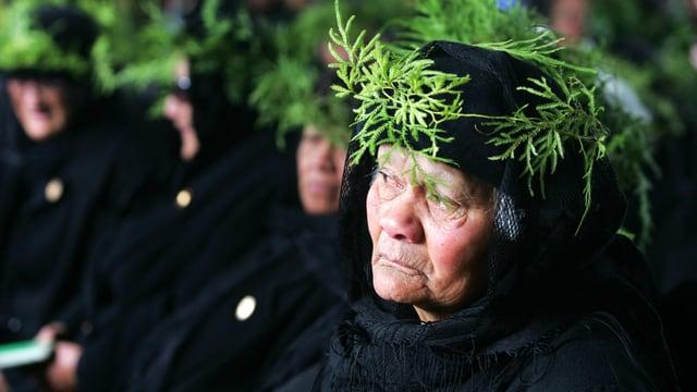 Eine ältere Frau in festlicher, Schwarzer Kleidung.