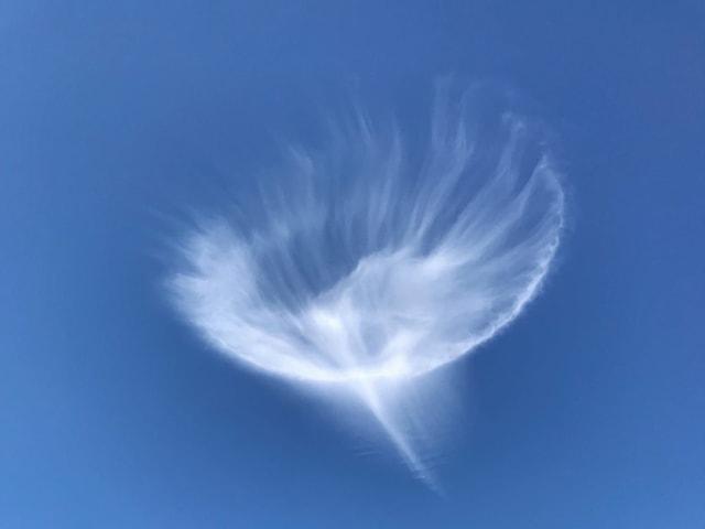 Feine haarähnliche Wolke in Quellen oder Trochterform am blauen Himmel.