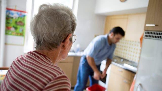 Ein jüngerer Mann arbeitet in der Küche einer älteren Frau.