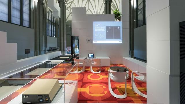 Blick in einen Museumsraum mit orangefarbenem Teppich.