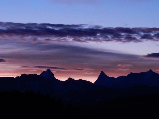 In der unteren Bildhälfte ist es dunkel. Am Horizont sind die markanten, spitzigen Silhouetten von Schreckhorn und Finsteraarhorn zu erkennen. Darüber ein Himmel mit zartrosanen Wolkenfelder.