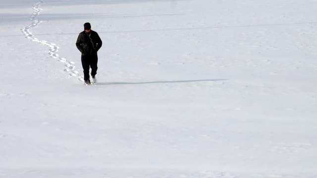 Mann, der über ein verschneites Feld geht.