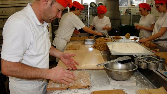 Bäcker in Backstube. Sie machen Biber.