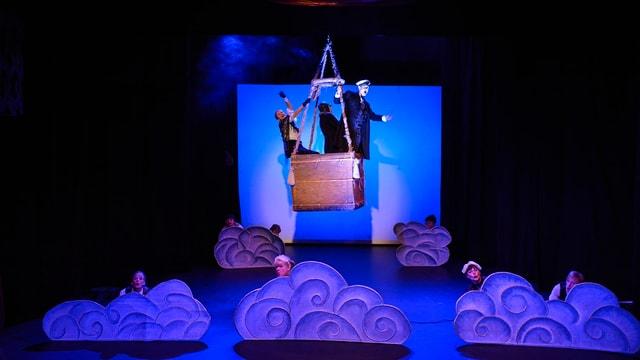 Ein Ballonkorb schwebt über die Bühne. Darin drei Leute, welche die Aussicht geniessen.