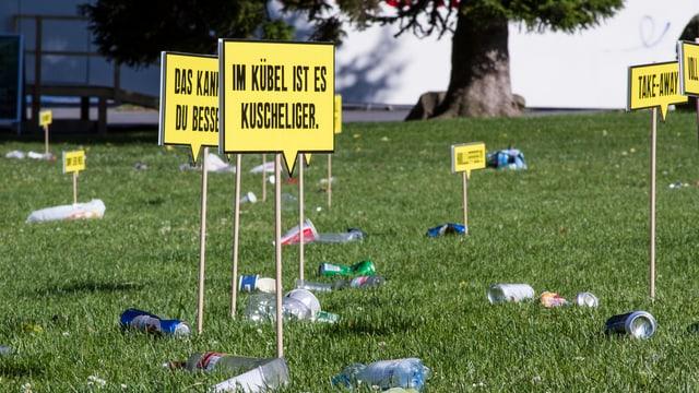 Plakate und Abfall auf der Wiese.
