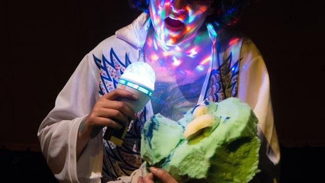 Eine Person hält eine grüne Puppe und ein buntes Licht in den Händen