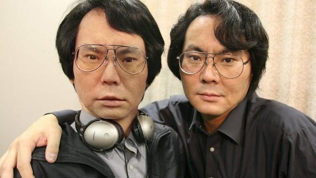 Zwei gleich aussehende Männer umarmen sich, wobei der ein Mensch, der andere ein Roboter ist.