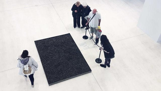 Einige Leute stehen im Museum vor einem Kunstwerk auf dem Boden.