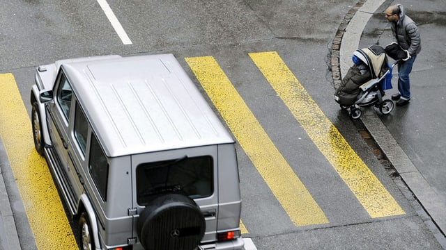 Ein Offroader überfährt einen Fussgängerstreifen trotz eines wartenden Vaters mit Kinderwagen.