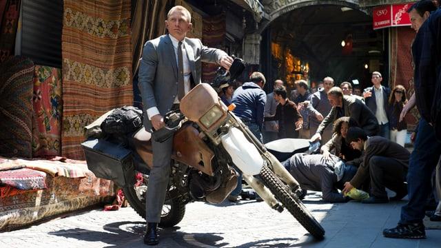 Ein Mann sitzt auf einem Motorrad, im Hintergrund ein Markt.