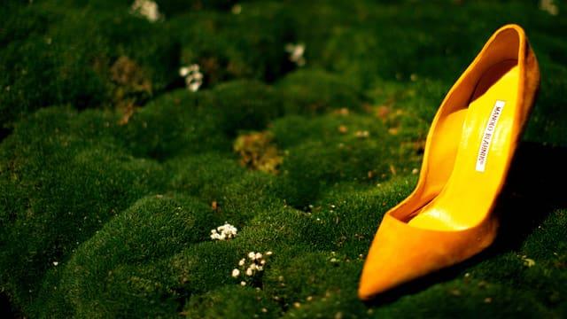 Ein Knallgelber Stöckelschuh steht auf einer moosbewachsenen Unterlage.