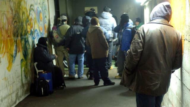 Menschen von hinten, die in einem Betongang auf ein Einlass warten.