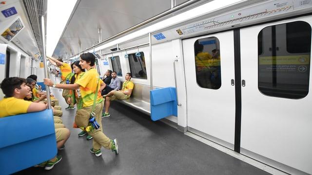 Menschen sitzen und stehen in einem Zug.