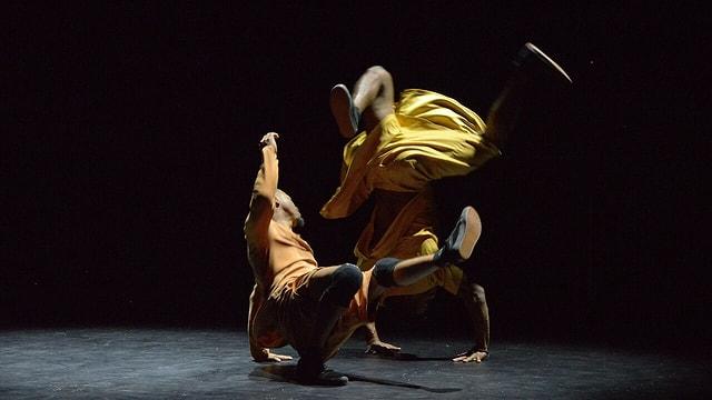 Zwei Männer in Röcken tanzen auf dem Boden auf einer dunklen Bühne.