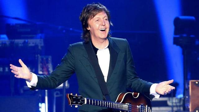 Ex-Beatle Paul McCartney steht mit einem Lachen auf der Bühne.