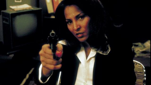 Filmszene Eine Frau sitzt in einem Stuhl und richtet ein Pistole auf den Betrachter.