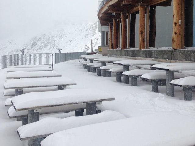 Eine Schneedecke auf den Bänke und Tischen eines Restaurants