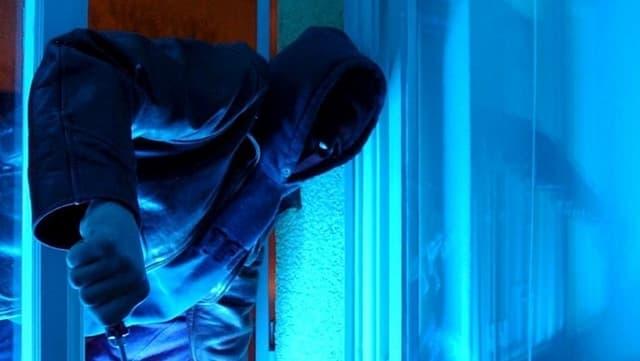 Ein Einbrecher steigt durch ein geöffnetes Fenster