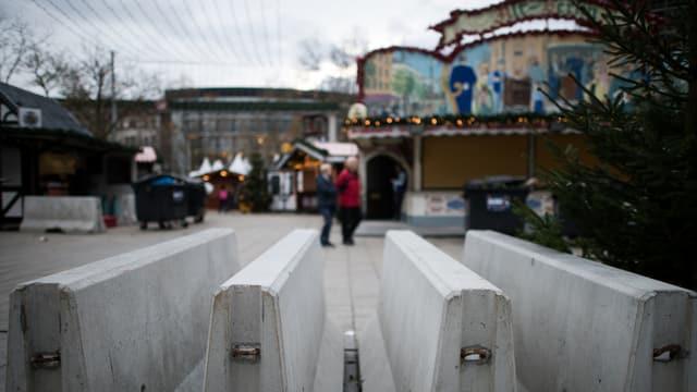 4 schwere Betonsperren, im Hintergrund der Berliner Weihnachtsmarkt.