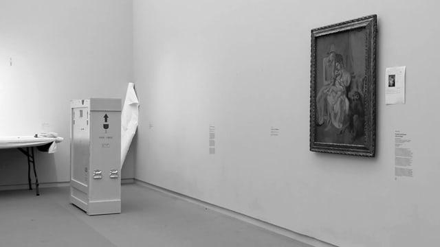 Schwarzweissaufnahme: Ein Bild hängt an der Wand, daneben steht eine grosse Holzkiste