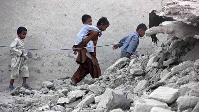 Drei Kinder laufen in einer Reihe hintereinander her. Sie sind umgeben von Betontrümmern.