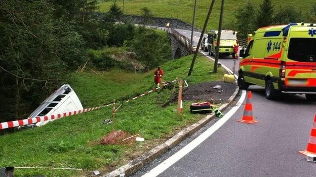 Ein Bus liegt in einem Strassengraben, daneben ein Ambulanzfahrzeug.