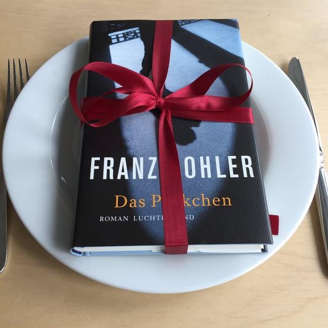 Das Buch «Das Päckchen» liegt auf einem weissen Teller mit einer Geschenkmasche drum