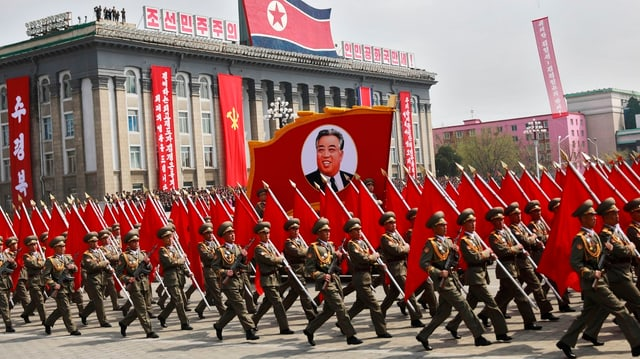Schuldada che marscha cun in placat da Kim Il Sung.
