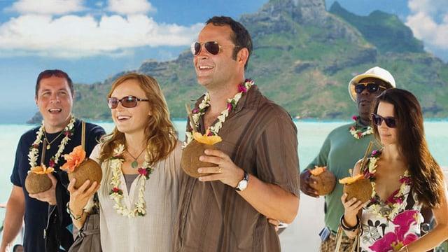 Drei Männer und zwei Frauen mit Kokosnuss in der Hand an einem Strand.