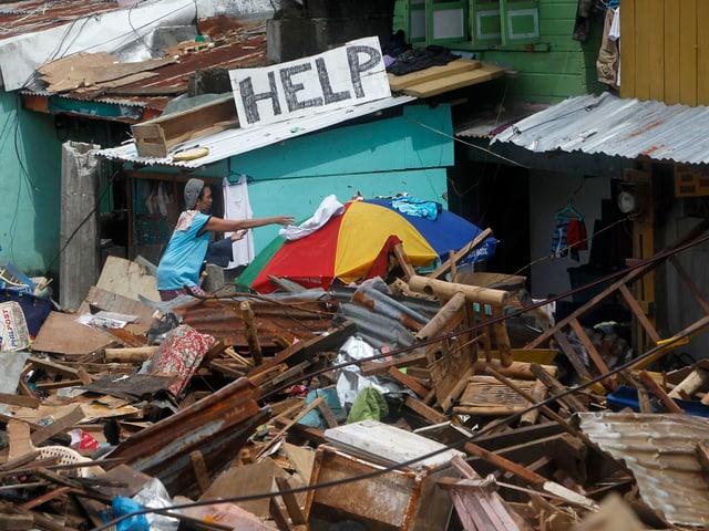 Ein Mann versucht in den Trümmern Kleider zu trocknen. Hinter ihm prangt ein grosses Schild mit der Aufschrift «Help».