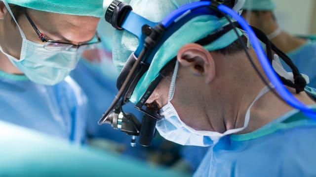 Nahaufnahme von zwei Ärzten während einer Operation mit Mundschutz.