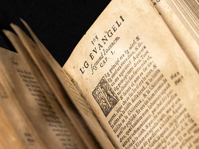 Eine sehr vergilbte Seite der Bibel mit rätoromanischem Text
