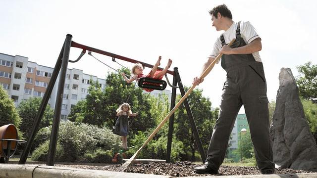 Ein Hausmeister recht auf einem Spielplatz. Kinder schaukeln und sehen glücklich aus.